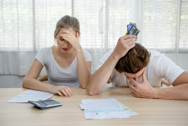 Young caucasian couple worried need help in stress at home living room sofa accounting debt bills bank papers expenses and payments feeling desperate in bad financial situation and bankruptcy. Premium Photo