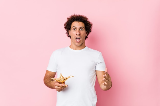 Young caucasian curly man  holding a magic lamp celebrating a victory or success Premium Photo
