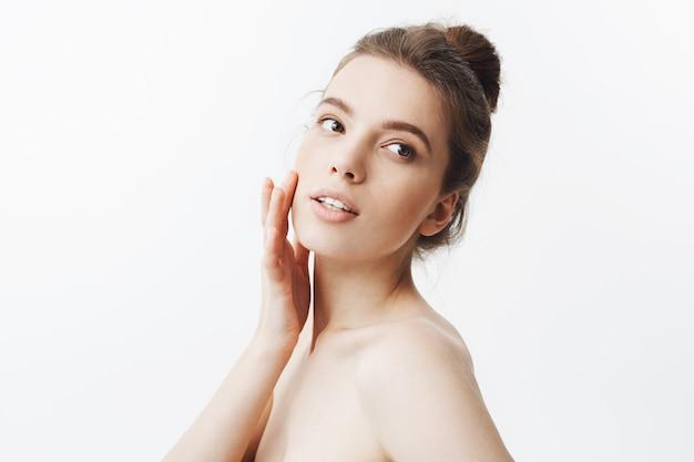 Молодой кавказской темноволосый студент девушка с булочкой прическа и обнаженное тело касаясь кожи на лице с пальцами, смотрю в сторону со спокойным и расслабленным выражением лица. Бесплатные Фотографии