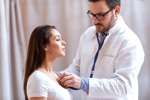 聴診器を使用して患者の肺を検査する若い白人医師。目を閉じて深呼吸している患者。 Premium写真