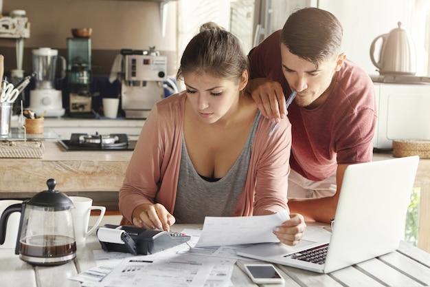 Молодая кавказская семья столкнулась с проблемой кредитной задолженности. красивая женщина держит лист бумаги и считает финансы Бесплатные Фотографии