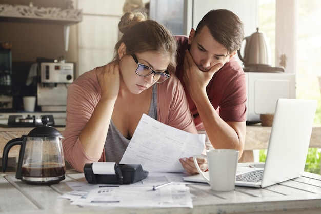 Young caucasian family having debt problems, not able to pay out their loan. female in glasses and brunette man studying paper form bank while managing domestic budget together in kitchen interior Free Photo