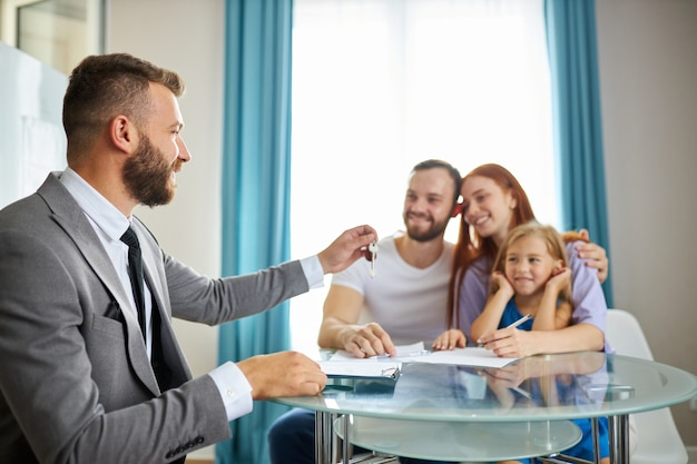Young caucasian family with child get keys from their first flat Premium Photo