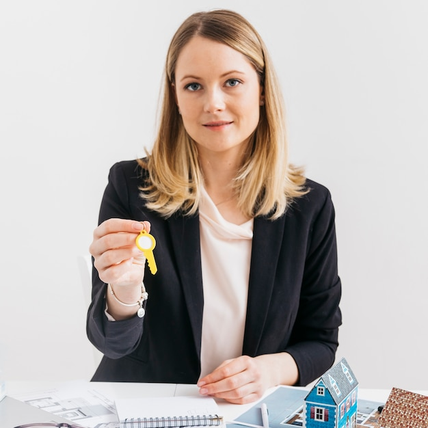 Young caucasian female real estate agent holding key looking at camera Free Photo