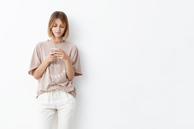 短い髪型の若い白人女性、さりげなく服を着て、携帯電話を手に取り、メッセージを入力し、イヤホンで音楽を聴く 無料写真