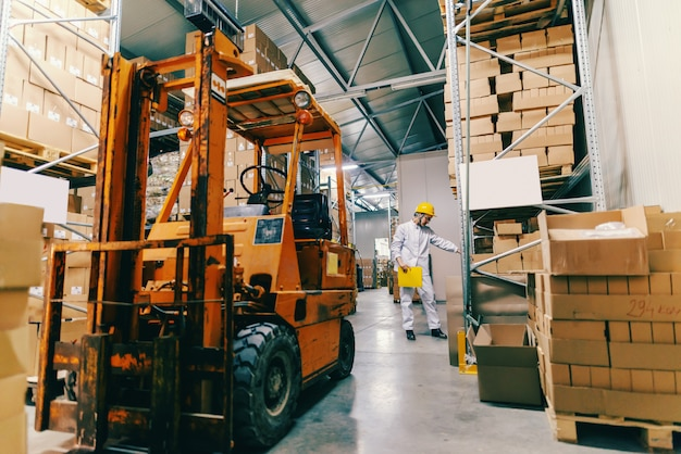 Young caucasian female worker in uniform and protective helmet holding folder and counting boxes. in foreground forklift. Premium Photo
