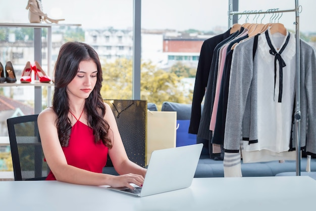 Young caucasian friendly woman working with laptop and selling online e-commerce shopping at clothes shop. Premium Photo