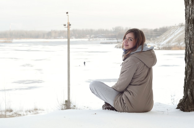 A young caucasian girl in a brown coat is sitting near a cliff Premium Photo