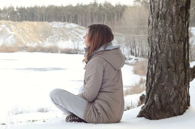 A young caucasian girl in a brown coat staring into the distance on the horizon line Premium Photo
