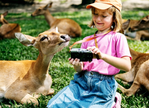 Young caucasian girl taking selfie with deers at the zoo Free Photo