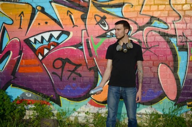 실버 에어로졸 스프레이와 검은 티셔츠에 젊은 백인 낙서 예술가 화려한 낙서 근처 수 있습니다 프리미엄 사진