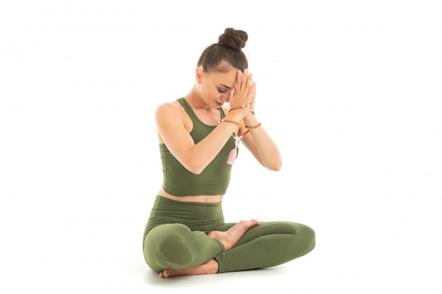 Young caucasian gymnast with athletic body sits on a floor in lotus position, doing yoga and meditating Premium Photo