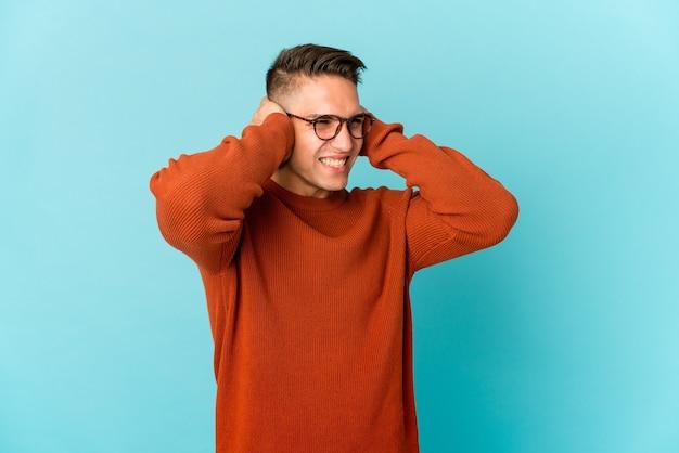 젊은 백인 잘 생긴 남자는 손으로 귀를 덮고 격리. 프리미엄 사진