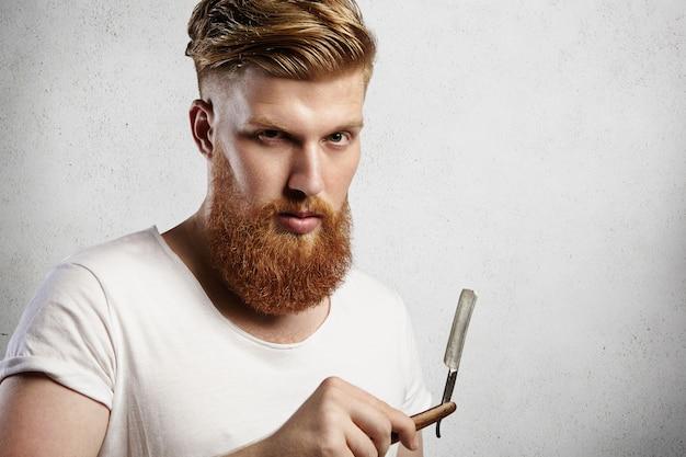 Молодой кавказский хипстерский мужчина в белой футболке пытается решить, сбрить ему длинную рыжую бороду или нет. стильный парень держит бритву с серьезным выражением лица и взглядом. Бесплатные Фотографии