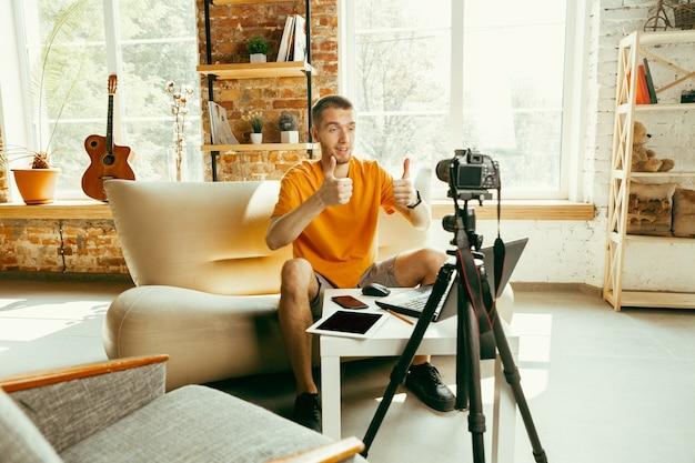 自宅でガジェットのビデオレビューを記録するプロのカメラを持つ若い白人男性ブロガー 無料写真