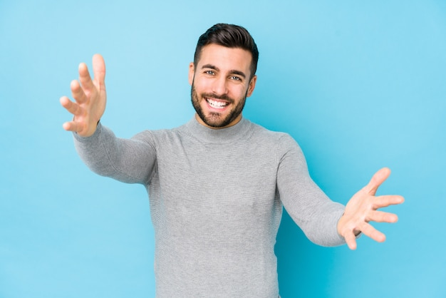 Young caucasian man against a blue wall isolated feels confident giving a hug to the camera. Premium Photo