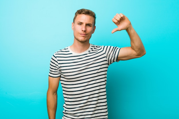 Young caucasian man against a blue wall showing a dislike gesture, thumbs down. disagreement concept. Premium Photo