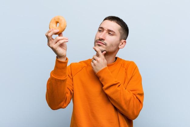 疑わしい懐疑的な表情で横向きのドーナツを保持している若い白人男性。 Premium写真