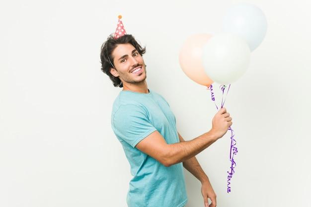 灰色の壁で分離されたbrithdayを祝う風船を保持している若い白人男 Premium写真