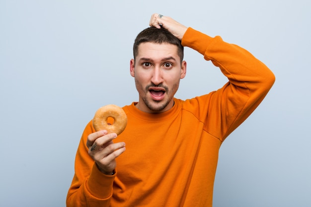 Young caucasian man holding a donut being shocked, she has remembered important meeting. Premium Photo