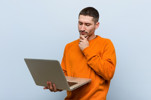 Young caucasian man holding a laptop looking sideways with doubtful and skeptical expression. Premium Photo