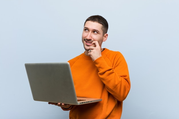 Young caucasian man holding a laptop relaxed thinking about something looking at a copy space. Premium Photo