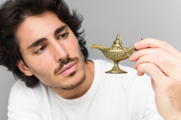 Young caucasian man holding a magic lamp isolated on a grey wall Premium Photo