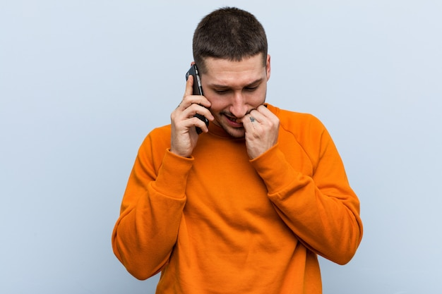 Young caucasian man holding a phone biting fingernails, nervous and very anxious. Premium Photo