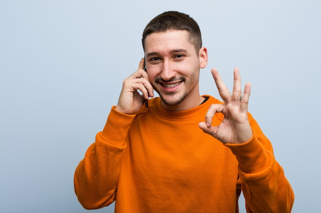 Young caucasian man holding a phone cheerful and confident showing ok gesture. Premium Photo