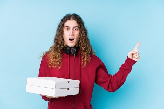 横を指して孤立したピザを保持している若い白人男性 Premium写真