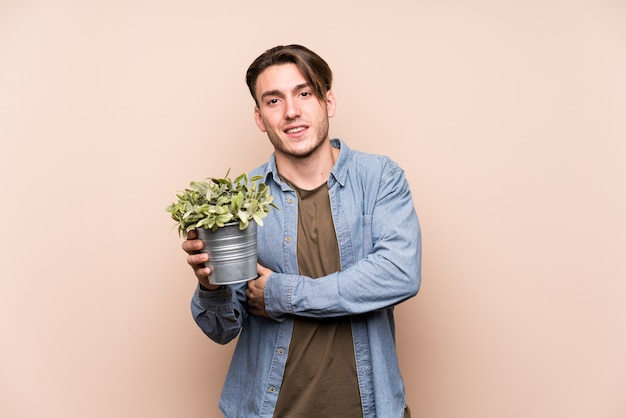 Young caucasian man holding a plant laughing and having fun. Premium Photo
