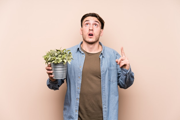 Young caucasian man holding a plant pointing upside with opened mouth. Premium Photo