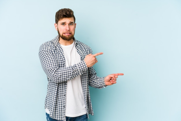 Young caucasian man isolated on blue wall shocked pointing with index fingers to a copy space. Premium Photo