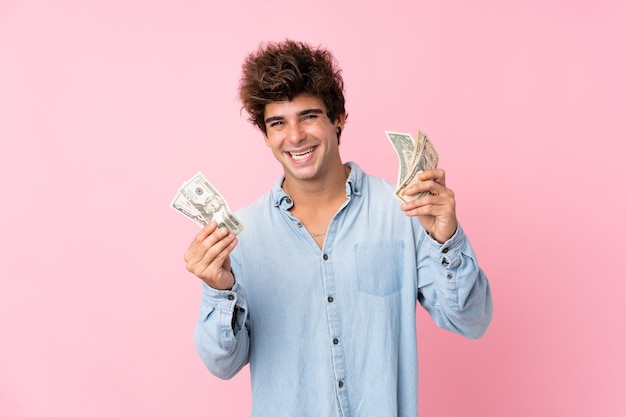 Young caucasian man over isolated pink wall taking a lot of money Premium Photo