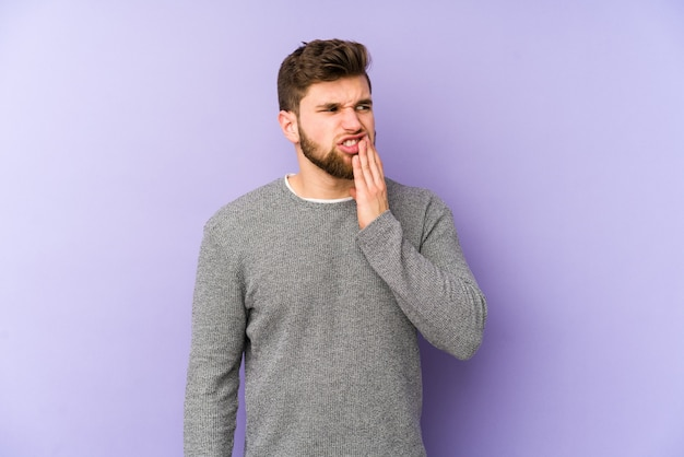 Young caucasian man isolated on purple space having a strong teeth pain, molar ache. Premium Photo