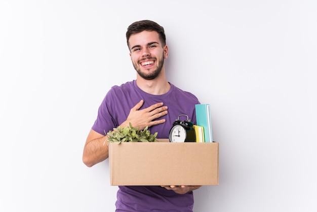 Молодой кавказский человек, перемещающий новый изолированный дом, громко смеется, держа руку на груди. Premium Фотографии