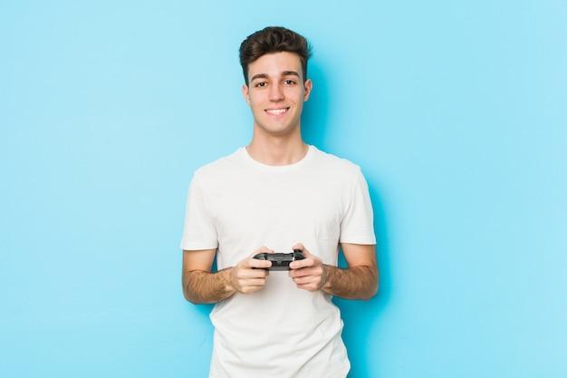 Молодой кавказский человек, играя в видеоигры с игровым контроллером, счастлив, улыбается и весел. Premium Фотографии