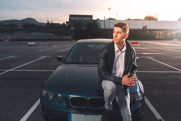 スポーツカーで駐車場でポーズをとる若い白人男性 Premium写真