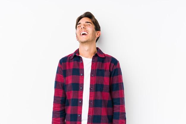Молодой кавказский мужчина позирует в розовой стене изолировал расслабленный и счастливый смех, вытянув шею, показывая зубы. Premium Фотографии
