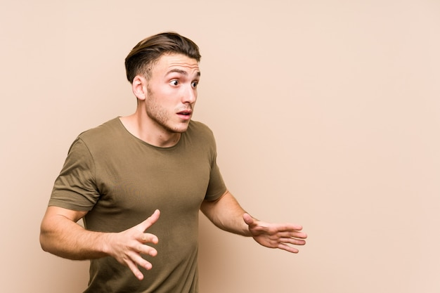 Young caucasian man posing isolated shouts loud, keeps eyes opened and hands tense. Premium Photo