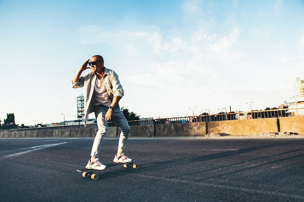 Young caucasian man riding on longboard or skateboard, modern shot in film grain effect and vintage style. Free Photo