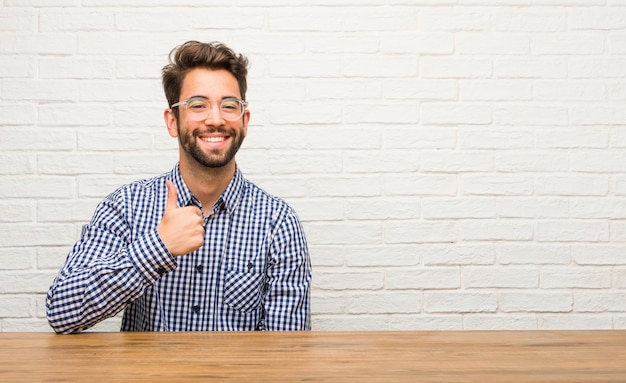 Young caucasian man sitting cheerful and excited, smiling and raising her thumb up, concept of success and approval, ok gesture Premium Photo