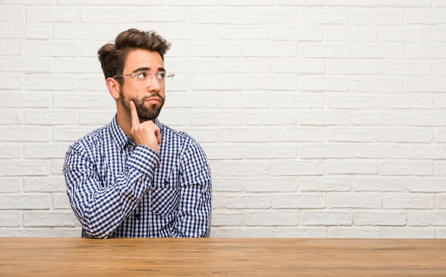 Young caucasian man sitting doubting and confused, thinking of an idea or worried about something Premium Photo