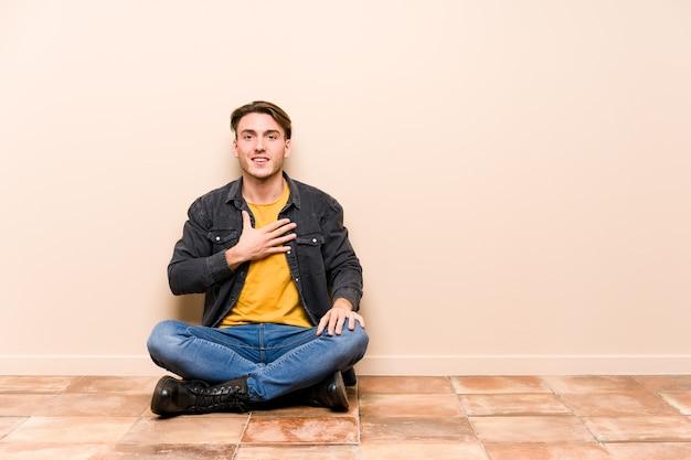 分離された床に座っている若い白人男性は大声で胸に手を置いて笑います。 Premium写真