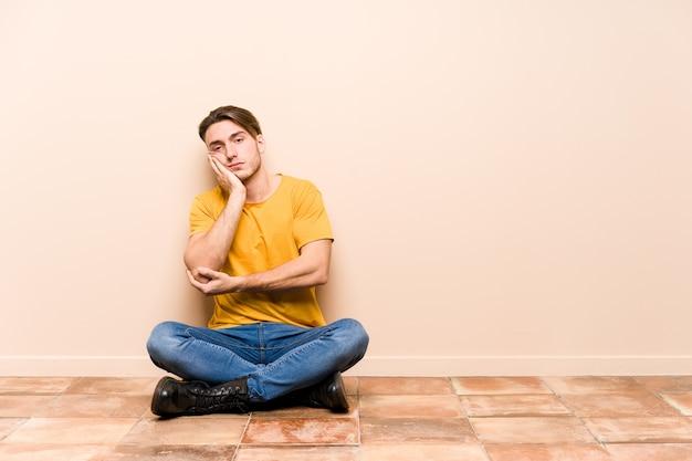 Молодой кавказский человек, сидящий на полу, изолировал себя, которому скучно, устал и нужен день отдыха. Premium Фотографии