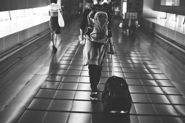 Young caucasian man travel with luggage in the airport Free Photo