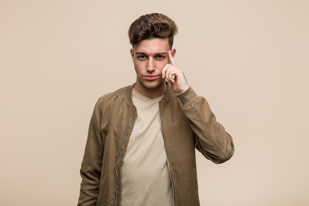 Young caucasian man wearing a brown jacket pointing temple with finger, thinking, focused on a task. Premium Photo