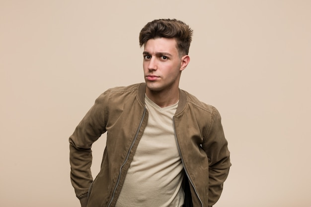 Young caucasian man wearing a brown jacket scolding someone very angry. Premium Photo