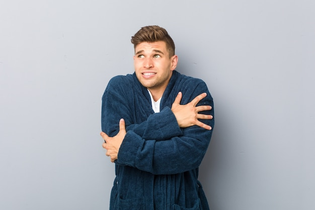 Young caucasian man wearing pajama going cold due to low temperature or a sickness. Premium Photo