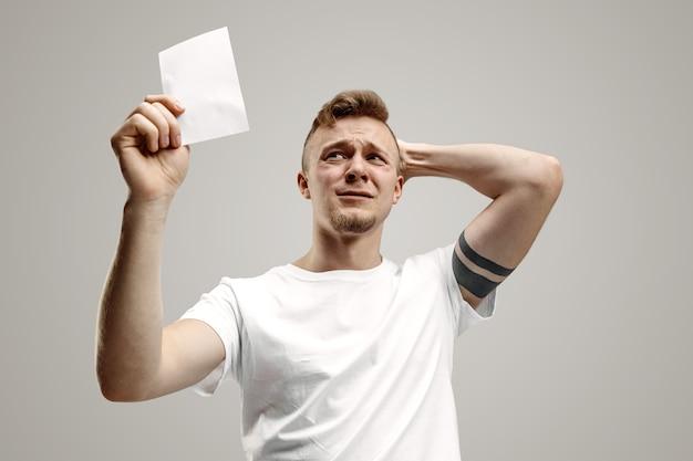 驚いた幸せな表情の若い白人男性が灰色の空間に賭けました 無料写真